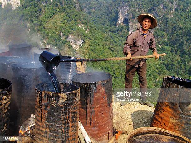 CONTENT] Road construction Worker is melting barrels of asphalt using fire wood In some regions of Asia road paving work is done with no machinery...