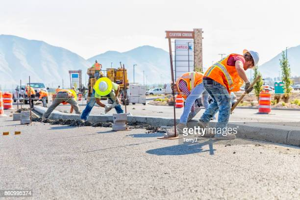 Road construction worker scoups up concrete while cleaning up a center medium just laid in Spanish Fork, Utah. Other workers smooth out the center medium with a float
