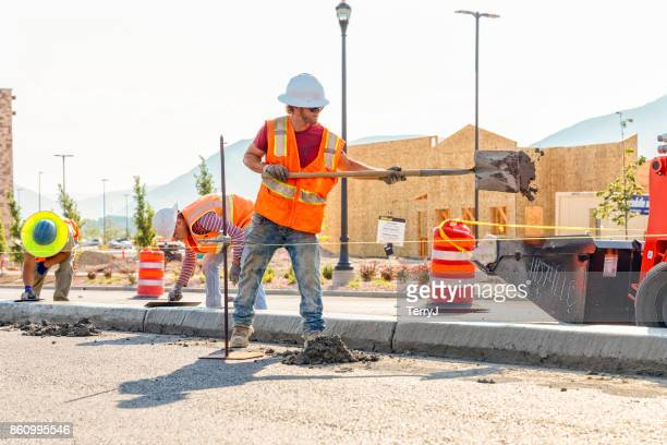 road construction worker throws a shovel full of concrete into a front-end loader while cleaning up a center medium just laid in spanish fork, utah - spanish fork utah stock pictures, royalty-free photos & images