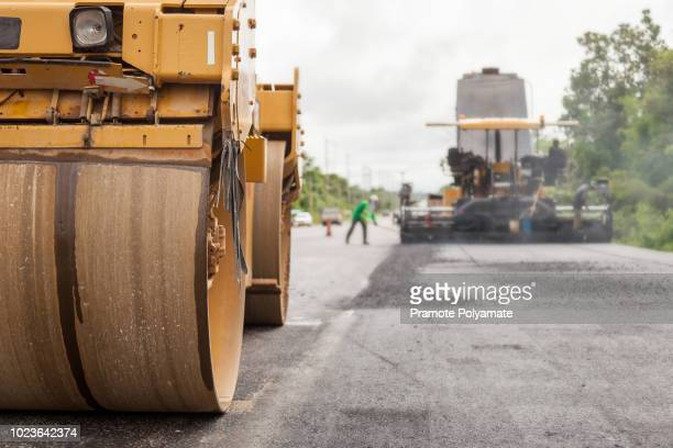 road construction works with roller compactor machine and asphalt finisher. - road construction stock pictures, royalty-free photos & images