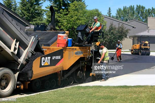 road crew and equipment in residential area - asphalt paving stock photos and pictures
