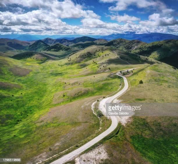 a road crosses the hilly landscape on the 'campo imperatore' plateau. - campo imperatore foto e immagini stock