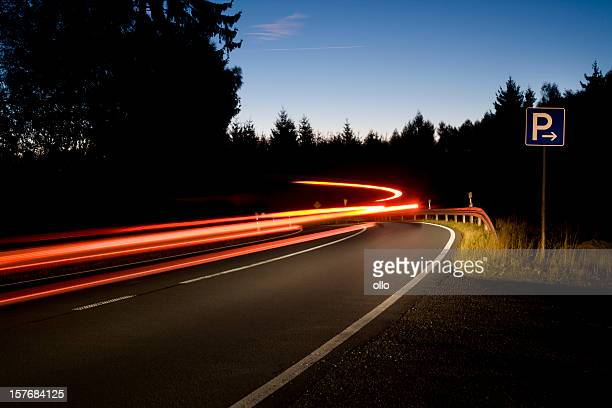 road curve at dawn, long exposure, passing car - letter p stock pictures, royalty-free photos & images