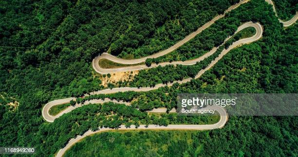 road curves from above - mountain road stock pictures, royalty-free photos & images