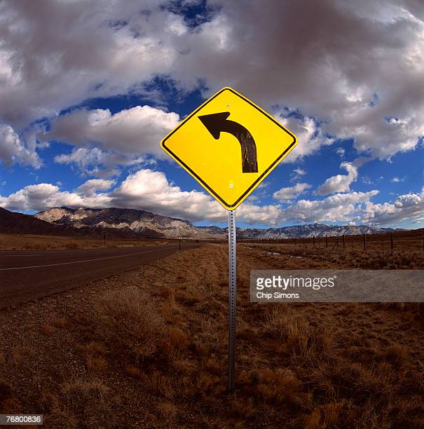 road curves left sign - curved arrows stock photos and pictures