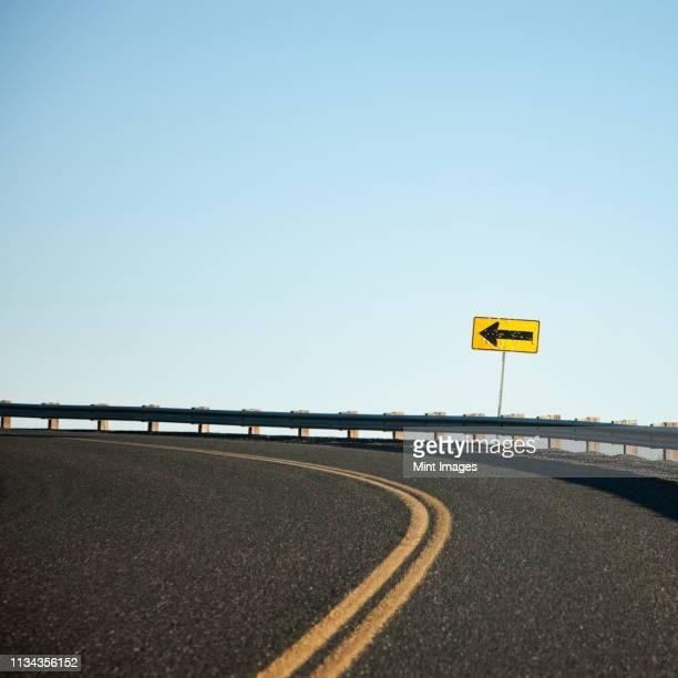road curving left - curved arrows - fotografias e filmes do acervo