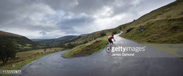 road cyclist climbing hairpin bends up hillside. - wielrennen stockfoto's en -beelden