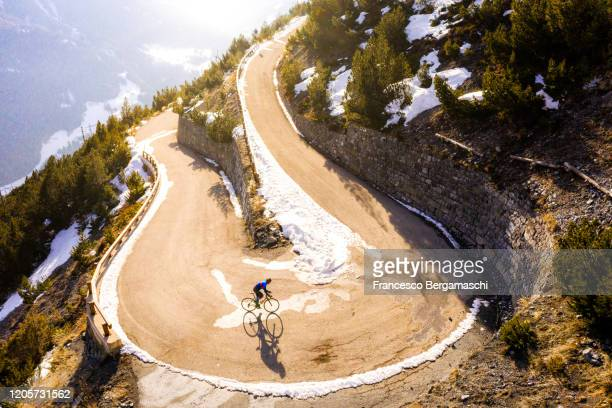 road cyclist climbing hairpin bends up mountain pass in winter with snow. - italia stockfoto's en -beelden