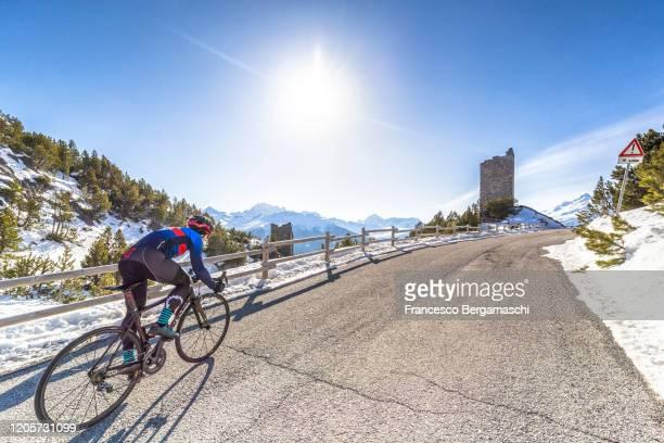 road cyclist climbing hairpin bends up mountain pass. - italia stockfoto's en -beelden