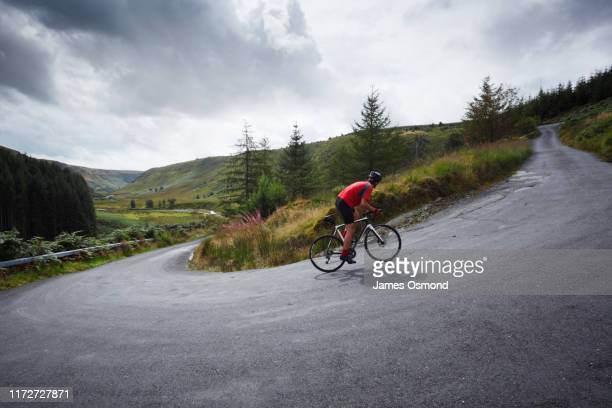 road cyclist climbing hairpin bends up steep road. - riding stock pictures, royalty-free photos & images
