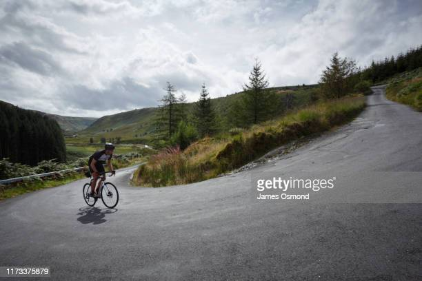 road cyclist climbing hairpin bends up steep road. - steep stock pictures, royalty-free photos & images