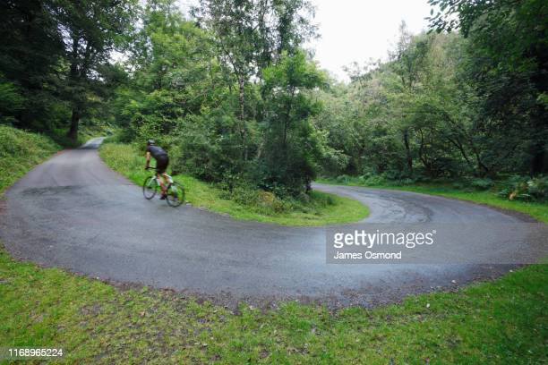 road cyclist cycling uphill round switchback in the road through woodland. - exmoor national park stock pictures, royalty-free photos & images