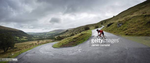 road cyclist descending round hairpin bend towards valley. - cycling stock pictures, royalty-free photos & images