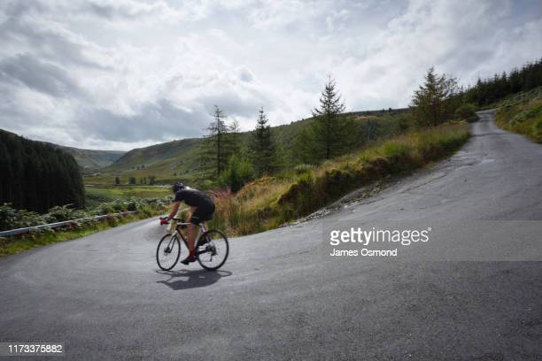 road cyclist descending round hairpin bend towards valley. - one mid adult man only stock pictures, royalty-free photos & images