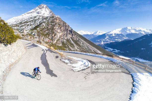 road cyclist descends from the winding road of an alpine pass in winter with snow. - italia stockfoto's en -beelden
