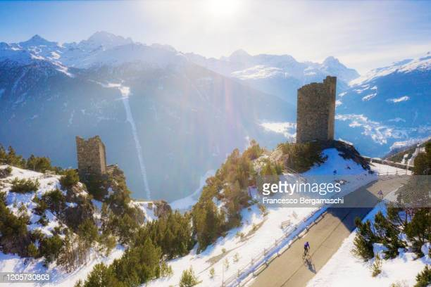 road cyclist pushing the road of a mountain pass in winter with snow illuminated by the sun. - italia stockfoto's en -beelden