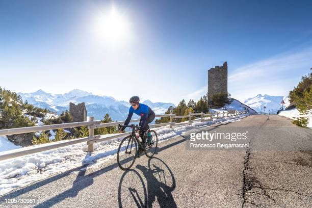 road cyclist rides on the road of an alpine pass in winter with snow. - italia stockfoto's en -beelden