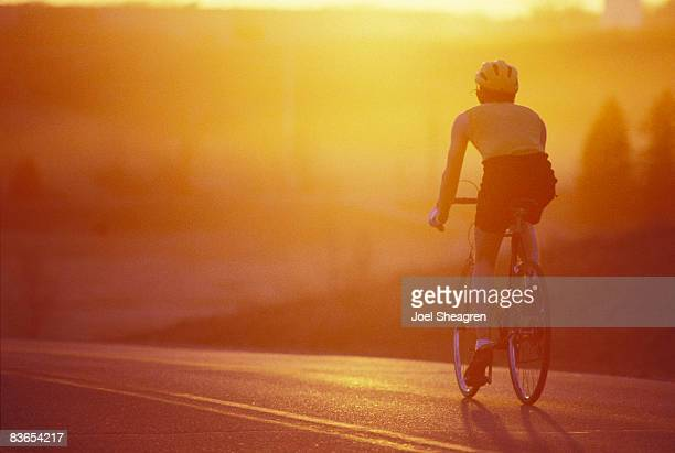 Road cyclists riding at sunset.