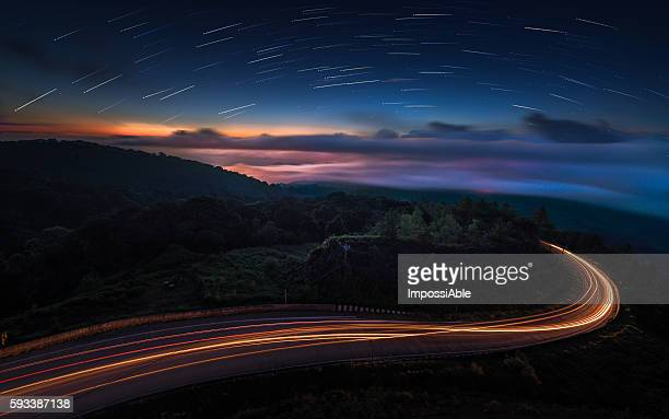 road downhill and startrail - impossiable stock pictures, royalty-free photos & images