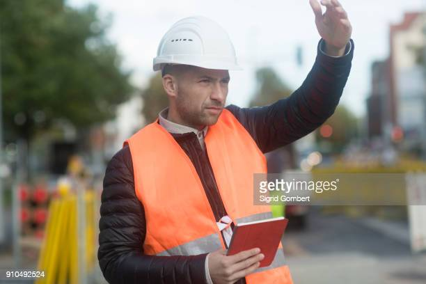 road engineer signalling with hand and holding digital tablet - sigrid gombert 個照片及圖片檔