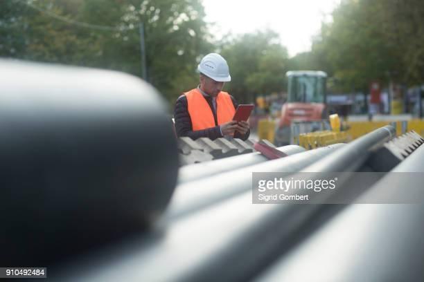 road engineer standing by pipes - sigrid gombert 個照片及圖片檔
