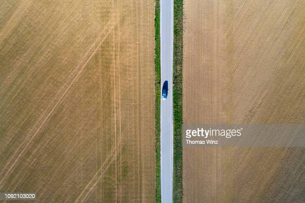 road from above through agricultural fields - 一本道 ストックフォトと画像