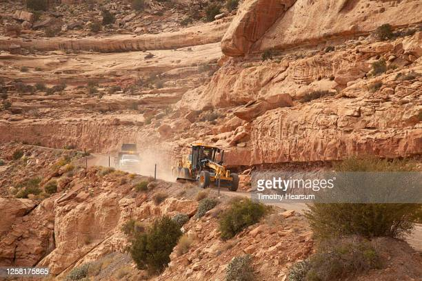 road grader and its tender work their way down a dirt road on the side of a red mesa - timothy hearsum fotografías e imágenes de stock