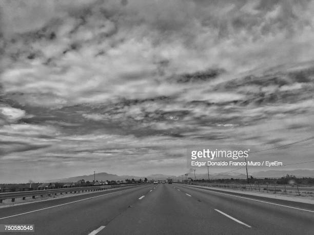road in city against sky - muro stock photos and pictures