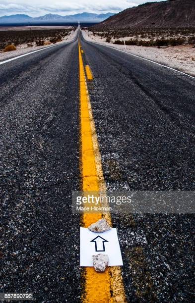 Road in Death Valley with arrow on double yellow line pointing towards infinity.