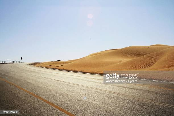 road in desert against clear sky - sand dune stock pictures, royalty-free photos & images