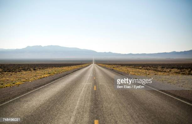 road in desert against clear sky - thoroughfare stock photos and pictures