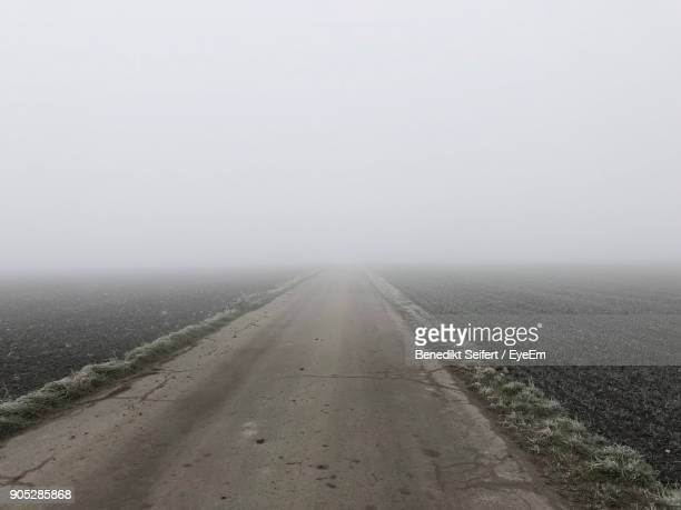 Road In Foggy Weather Against Sky During Winter