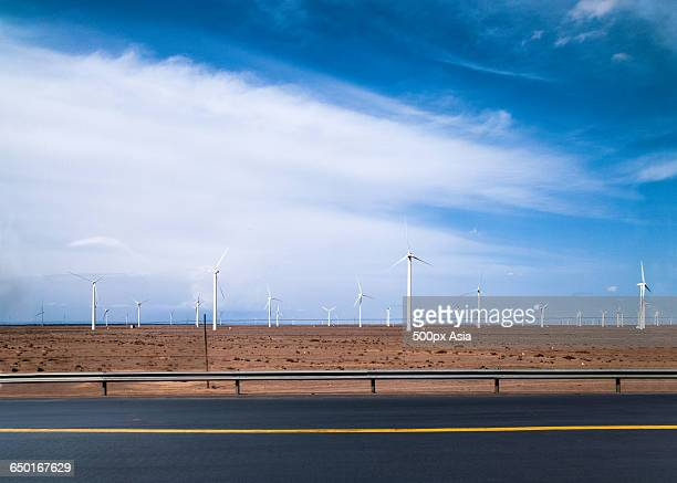 road in gansu with wind turbines in background - gansu province stock pictures, royalty-free photos & images