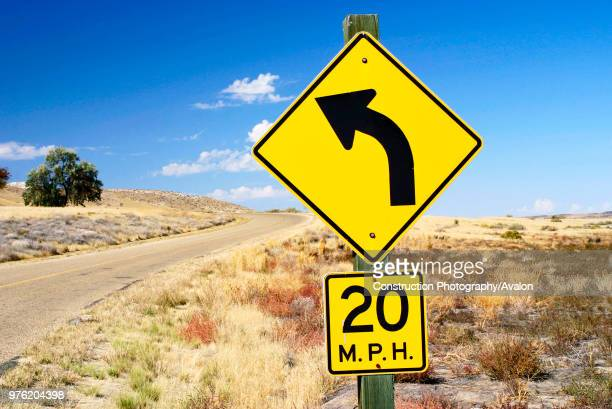Road in Idaho USA warning to reduce speed to 20 miles per hour while rounding the curve