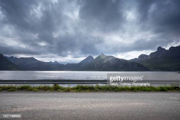 road in norway along a sea bay, side view - van de zijkant stockfoto's en -beelden