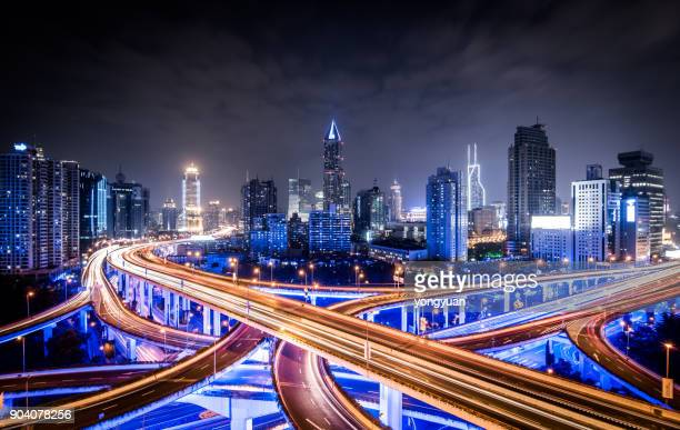 road intersection at night - illuminate stock photos and pictures