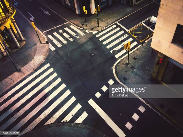 road intersection in city taken from high angle view without people, nice street geometry and white crosswalk in contrast of black asphalt. - crossroad stock pictures, royalty-free photos & images