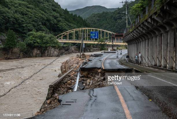 Road is rendered unappeasable after partially collapsing into the Kuma River after flooding caused by torrential rain, on July 6, 2020 in Kuma,...