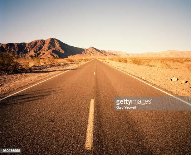 road leading into desert landscape - 荒野 ストックフォトと画像