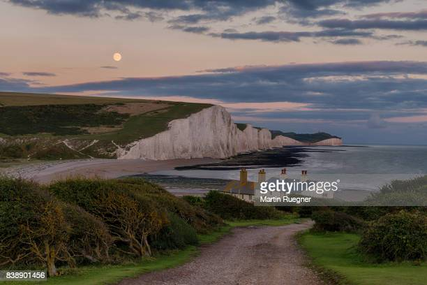 road leading to seven sisters chalk cliffs from cuckmere haven beach, with moon. - seven sisters cliffs stock photos and pictures