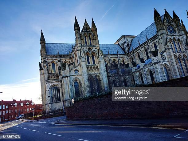 road leading towards beverley minster against sky on sunny day - minster stock photos and pictures