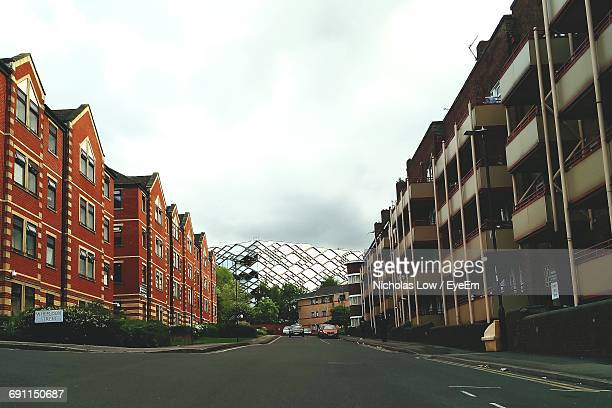 road leading towards buildings against cloudy sky - sheffield stock pictures, royalty-free photos & images