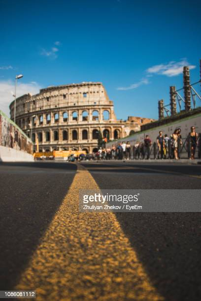 road leading towards coliseum against blue sky - coliseum rome stock photos and pictures
