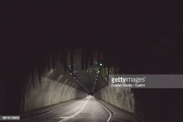 road leading towards illuminated tunnel at night - bortes foto e immagini stock