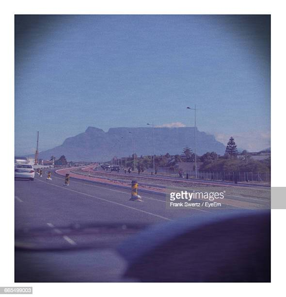 road leading towards mountain against sky seen through car windshield - frank swertz stockfoto's en -beelden