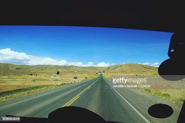 Road Leading Towards Mountain Seen From Bus Windshield