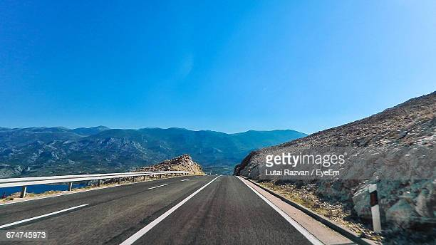 road leading towards mountains against clear blue sky - lutai razvan stock pictures, royalty-free photos & images