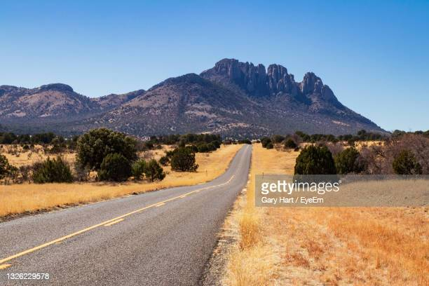road leading towards mountains against clear sky - texas stock pictures, royalty-free photos & images