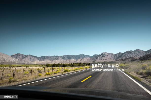 road leading towards mountains against clear sky seen through car windshield - christian soldatke stock pictures, royalty-free photos & images