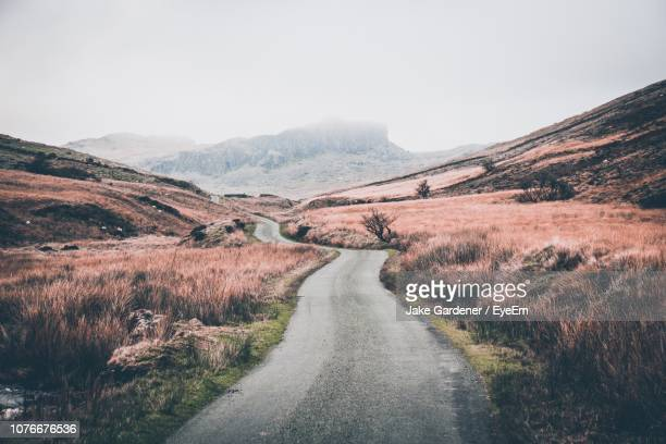 road leading towards mountains against sky - snowdonia stock photos and pictures